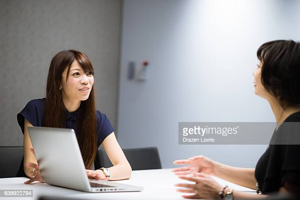 Two Japanese professional bankers discussing investent opportunites