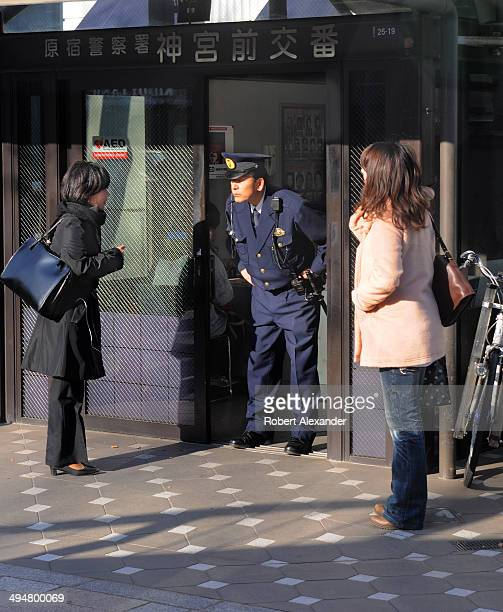 Two Japanese women ask a police officer for directions in Tokyo Japan