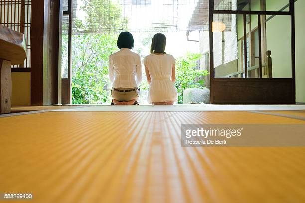 Two Japanese women contemplating the garden from the veranda