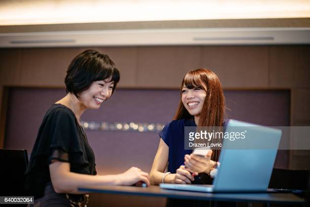 Two Japanese women discussing investments and  finances