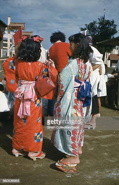 Two Japanese women in colorful kimonos viewed from behind standing in a crowd wearing traditional platform geta sandals Japan 1952