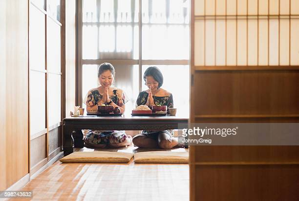 Two Japanese women in give thanks before eating meal