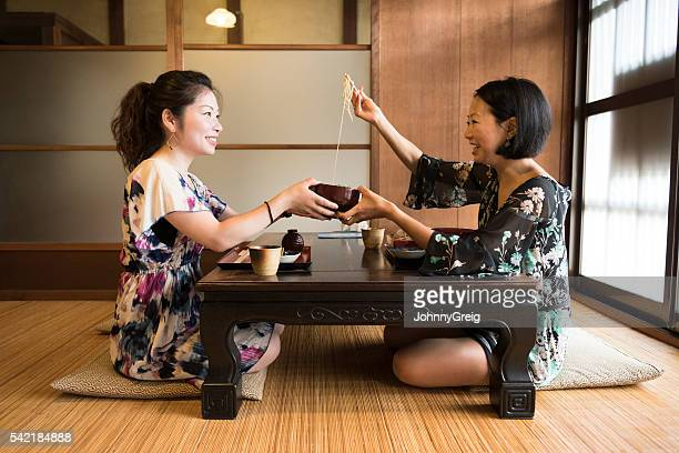 Two Japanese women in restaurant, one serving food