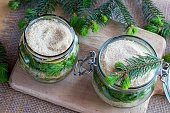 Two jars filled with young spruce tips, lemon and cane sugar, to prepare homemade syrup against cough