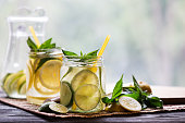 Two jars with homemade lemonade on wooden background