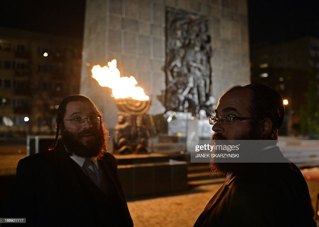 Two Jewish men stand in front of the monument to the fighters of the Warsaw ghetto uprising in Warsaw on April 18, 2013 waiting for an evening of commemorations on the eve of the 70th anniversary of the outbreak of the 1943 revolt. .