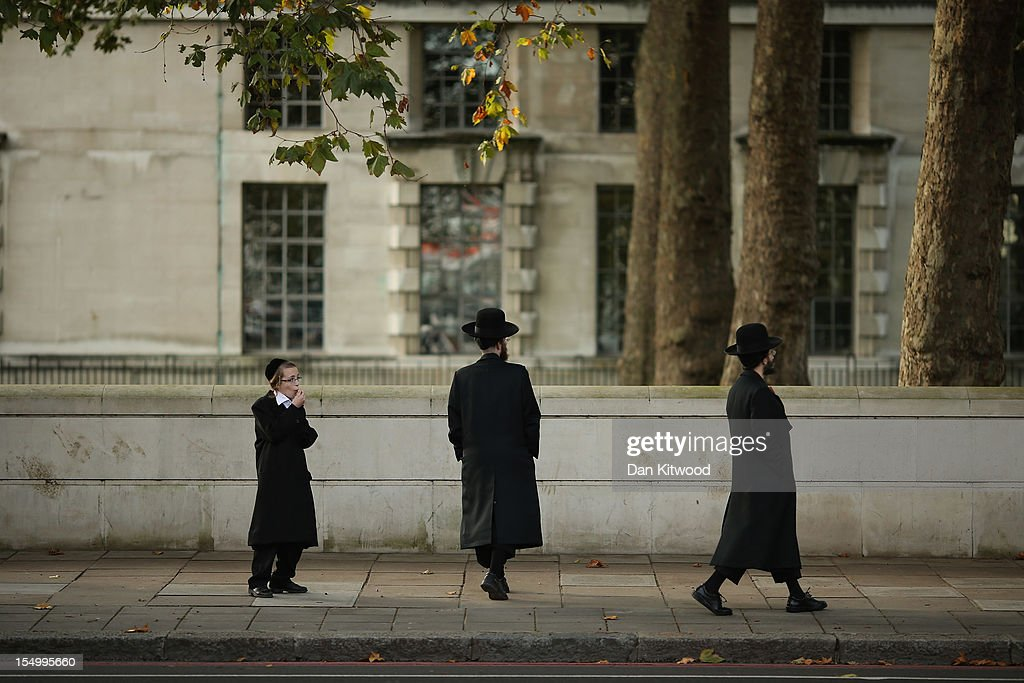 Two Jewish men walk along the Embankment with a younger Jewish boy on October 30, 2012 in London, England.