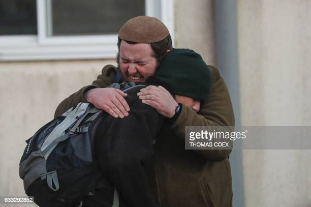TOPSHOT Two Jewish settlers embrace as Israeli security forces evict hardline residents from the wildcat Amona outpost northeast of Ramallah on...