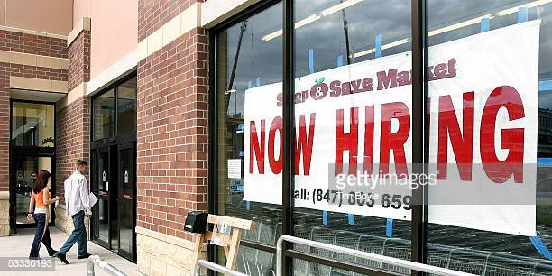 Two job applicants with their applications in hand walk past a Now Hiring sign into a new grocery store under construction August 5 2005 in Des...