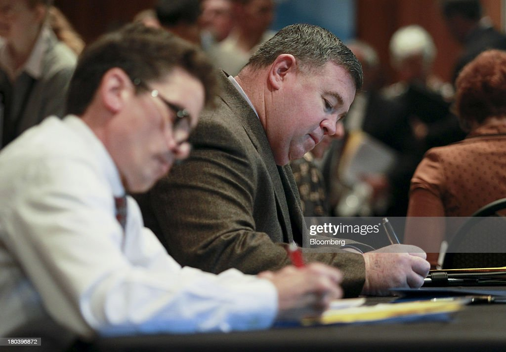 Two job seekers fill out applications at the annual Maximum Connections job fair in Portland, Oregon, U.S., on Thursday, Sept. 12, 2013. Jobless claims in the U.S. declined last week to the lowest level since April 2006 as work on computer systems in two states caused those employment agencies to report fewer applications. Photographer: Natalie Behring/Bloomberg via Getty Images