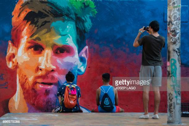 Two joung men look at a graffiti portraying Barcelona's Argentinian forward Lionel Messi as another one takes photos on June 17 2017 in Barcelona /...