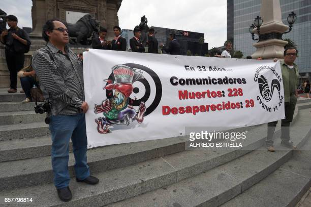 Two journalists hold a banner displaying the number of journalists dead and disappeared in the past 33 years in Mexico during a protest against the...