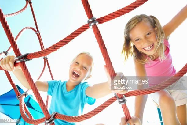 Zwei fröhliche Mädchen klettert am Seil Leiter gegen den Himmel