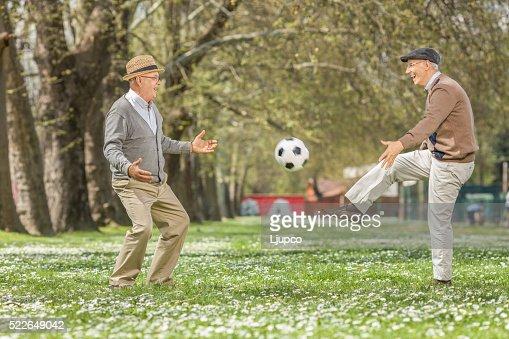 Dos ancianos Alegre jugando al fútbol en el parque : Foto de stock