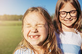 Two joyfull girls hugging and closed their eyes from the sun. Sincere emotion. Girls without front teeth.