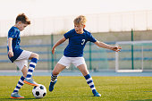 Two Junior Soccer Players Training with Soccer Ball on Stadium Grass Pitch