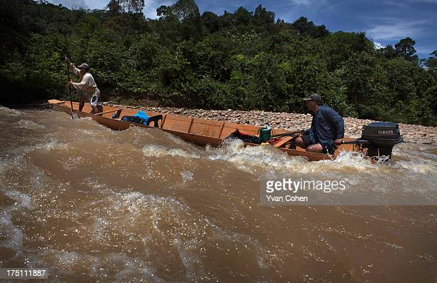 Two Kelabit men navigate their boat through a set of rapids on a river that passes through the village of Long Napir A new dam project supported by...