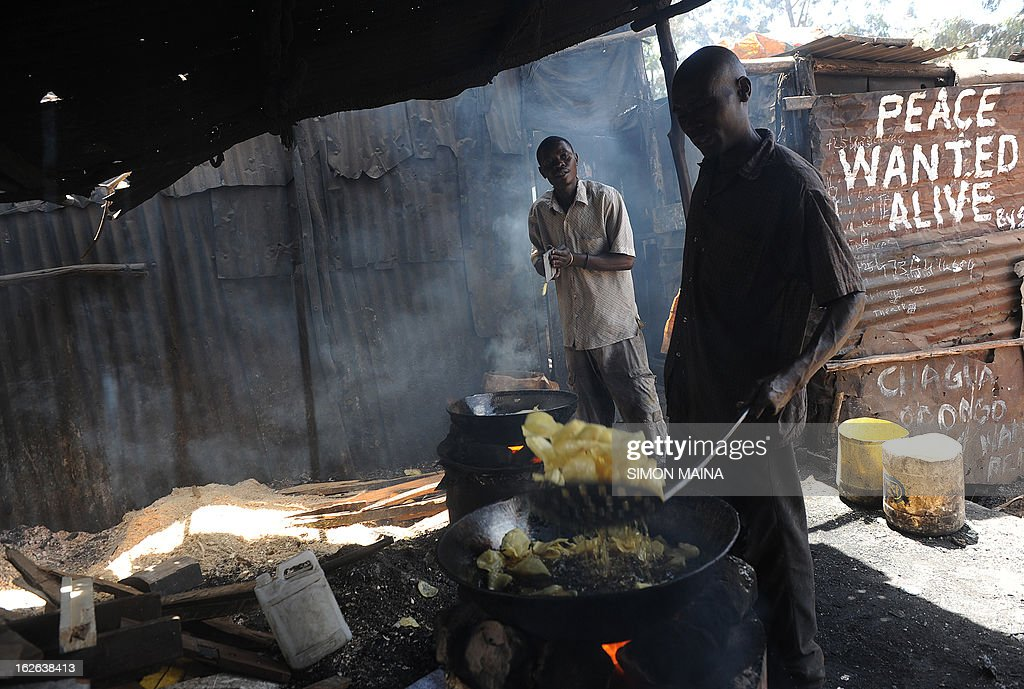 Two Kenyan men make crisps by the road side next to writing on an corrugated iron sheet house, urging for a peaceful poll on February,25,2013 in the sprawling Kibera slums. Kenya is gearing up for presidential, gubernatorial, senatorial elections on March 4, the first since bloody post-poll violence five years ago in which more than 1,100 people died after contested results. AFP PHOTO/SIMON MAINA