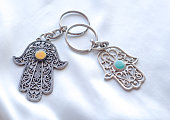 Two key rings in the form of Fatima Hand on a white silk background. Ancient symbol and traditional modern tourist souvenir of Tunisia.