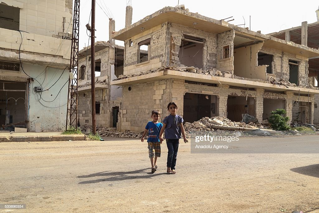 Two kid walk on the street in Kafr Zita Town of Hama, Syria on May 24, 2016. Assad regime forces had been hitting the town since 2012 continuously. Most of the residents fled from attacks and left the collapsed town.