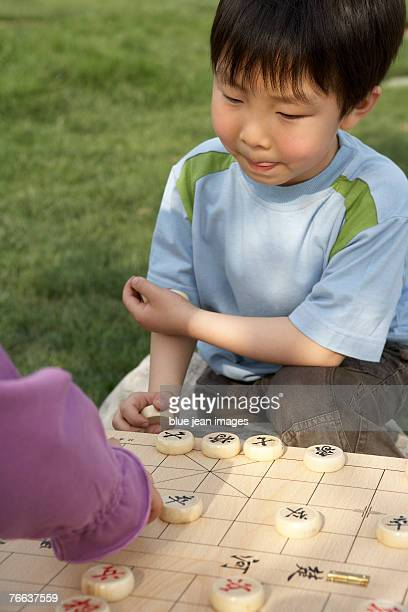 Two kids are playing Chinese chess.