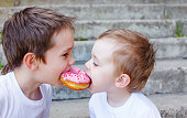 two boys together bite from the donut. children enjoy a donut with strawberry frosting. divide the a donut in half. feeding game for party