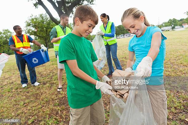 Two kids collecting and throwing away garbage with volunteer team