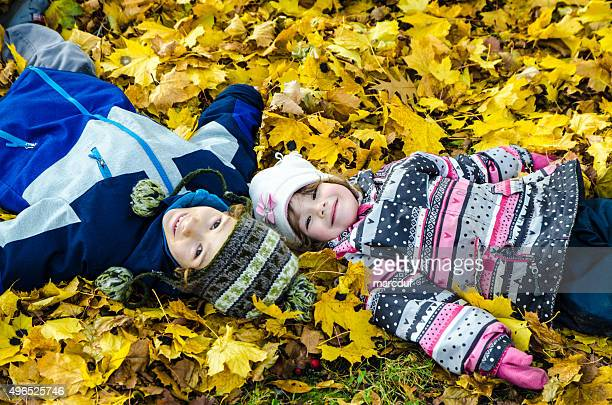 Two kids having fun with autumn leaves