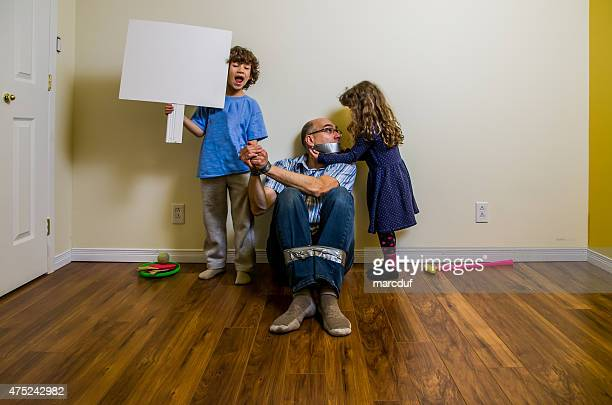 Two kids having their father as hostage with duct tape