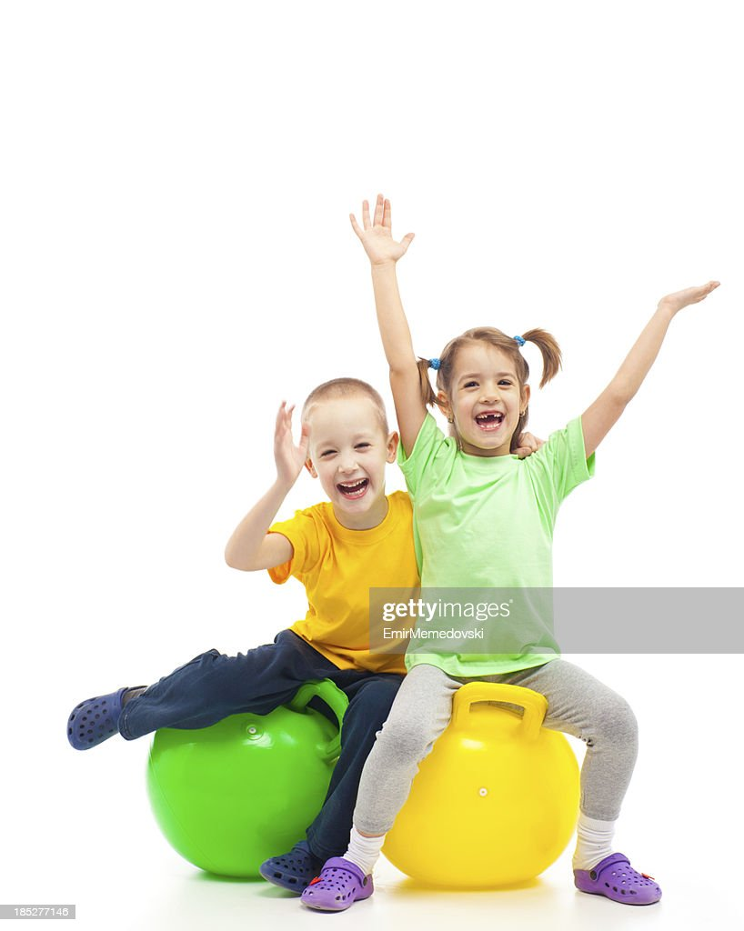 two kids heaving fun with bouncing ball