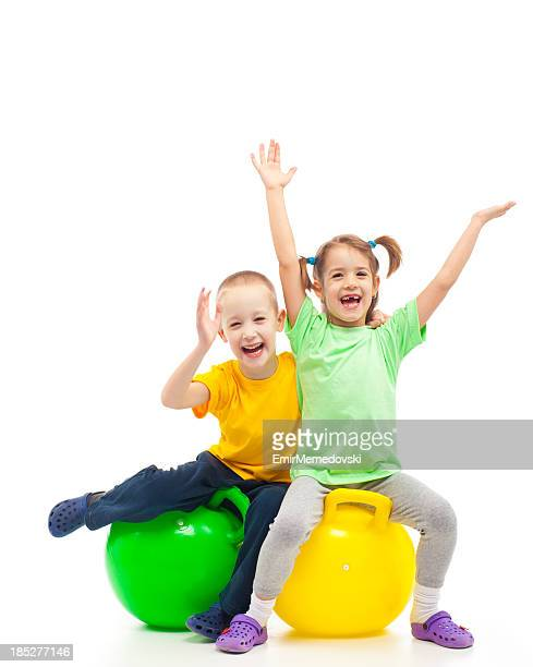 two kids heaving fun with bouncing ball