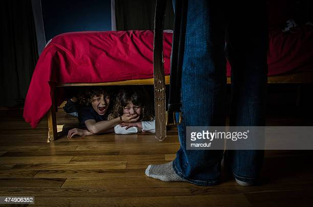 Two kids hidden under bed crying out of fear