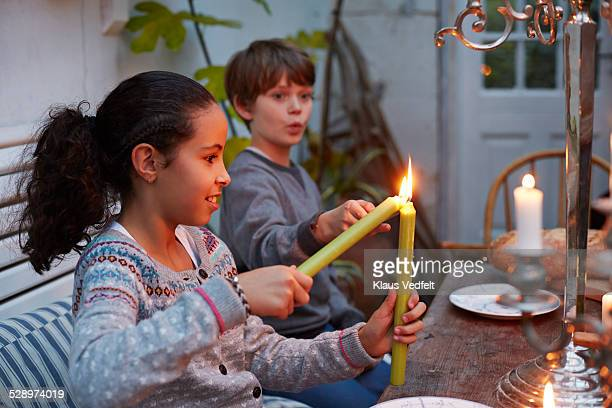 Two kids lighting candles in greenhouse