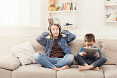 Two kids with gadgets. Sister and brother sharing funny content on digital tablet and listening to music in hearphones on sofa at home. Family friendship and communication concept
