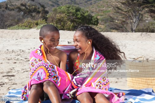 Two kids listening to headphones on beach : Stockfoto