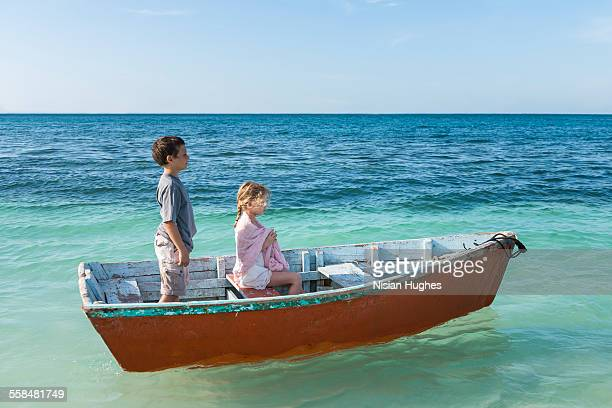 Two kids on small boat in ocean