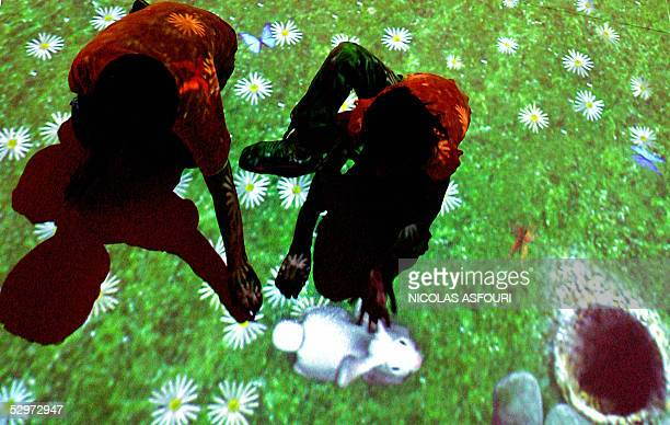 Two kids play in the virtual garden trying to catch a rabbit in the House of the Futur exposed at the museum of communication 24 May 2005 in Lisbon A...