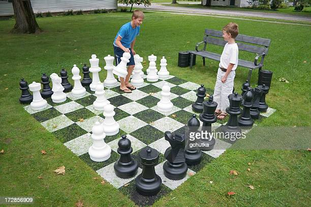 Two kids playing a chess game with large pieces on grass