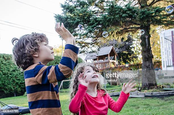 Two kids playing with soap bubble outside