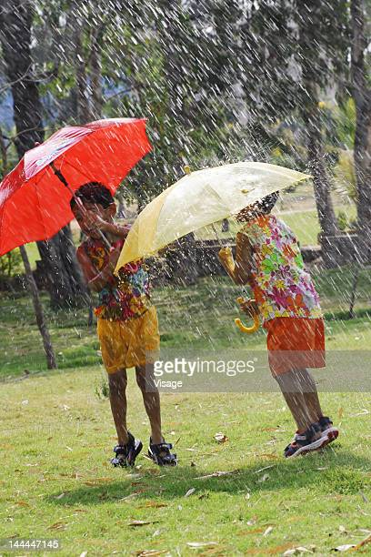 Two kids playing with umbrellas
