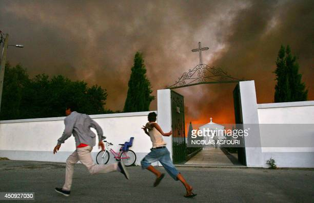 Two kids run away from the flames of a wild fire approaching their village in Lapa do Lobo 300 km north of Lisbon 02 October 2005 Forest fires flared...