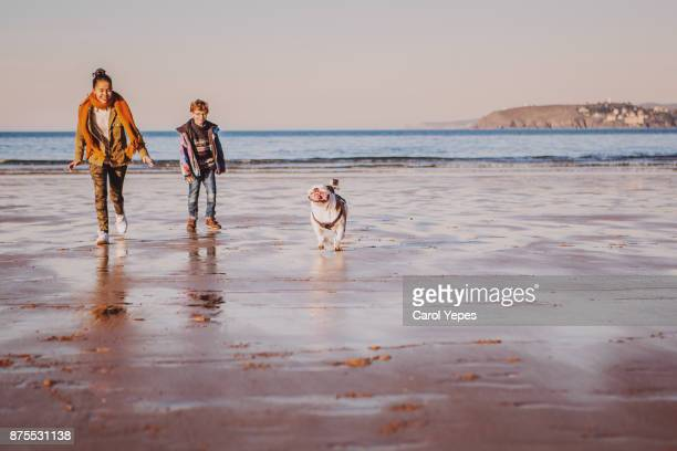 two kids running at the beach with the dog