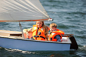 Sister and her brother with down syndrome are sailing in a small boat.