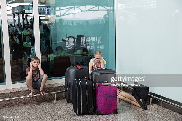 Two kids sit as they wait flight schedule information at Ngurah Rai International airport on July 10 2015 in Denpasar Bali Indonesia 277 flights...