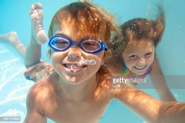 Zwei Kinder lächelnd unter Wasser im pool