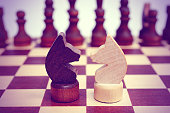 Two knight on a chessboard. Light and dark. Confrontation. Against each other. Forehead to forehead. Vintage toning.