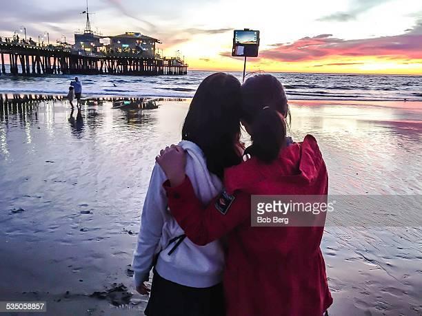 Santa Monica Ca January 22 2015 Two Korean tourists take a friends selfie with a selfie stick on the Santa Monica pier beach at sunset
