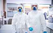 Portrait of two lab workers in protective overalls, glasses and masks
