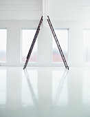 Two ladders in white empty room