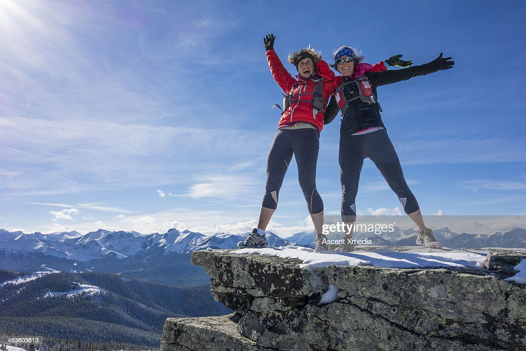 Two ladies celebrate success together on mt summit : Stock Photo